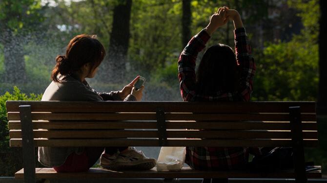 Freundinnen sitzen auf der Bank, eine schaut auf ihr Handy