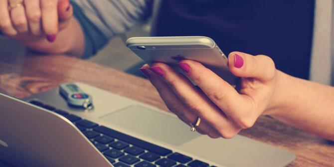 Multitaskende Frau mit Handy vorm Laptop
