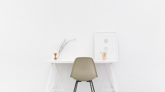 Weißer aufgeräumter Schreibtisch vor weißer Wand
