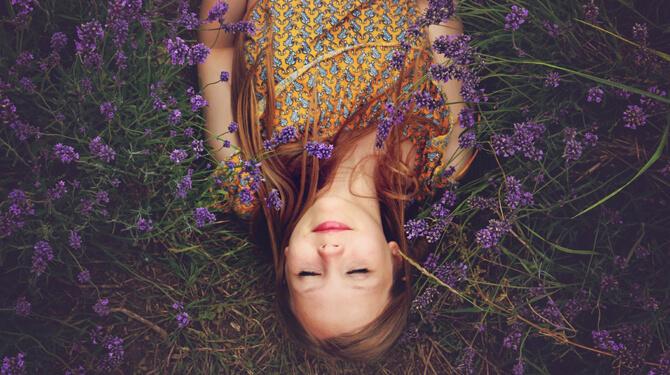 Frau liegt mit geschlossenen Augen im Gras