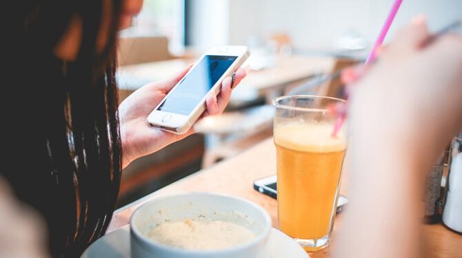 Frau frühstückt mit Handy in der Hand