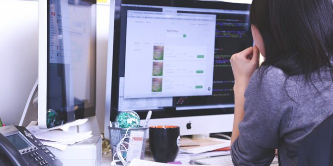 Frau im Büro vor Bildschirmen