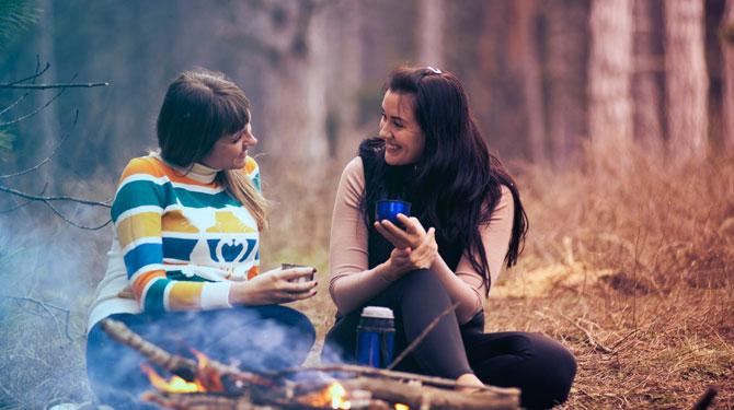 Zwei Frauen im Gespräch am Lagerfeuer