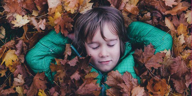 Junge liegt ohne Smartphone mit geschlossenen Augen im Laub