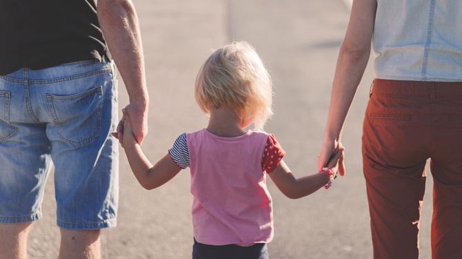 Kind mit Eltern an der Hand
