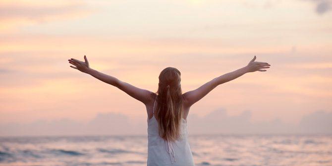 Frau am Strand mit ausgebreiteten Armen, befreit von ihren Glaubenssätzen