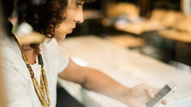 Frau kontrolliert am Handy das Profil eines anderen