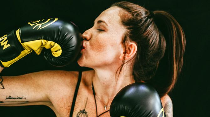 Frau hat sich aus der Standby-Falle befreit und küsst ihren Boxhandschuh