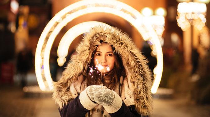 Frau mit Wunderkerze in der Neujahrsnacht mit vielen Vorsätzen fürs neue Jahr.