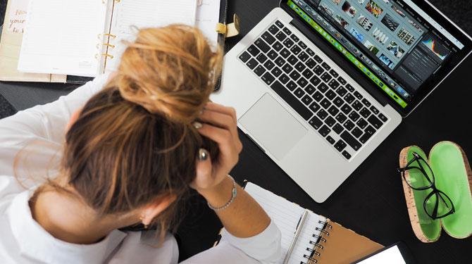 Gestresste Frau mit FOMO am vollgepackten Schreibtisch