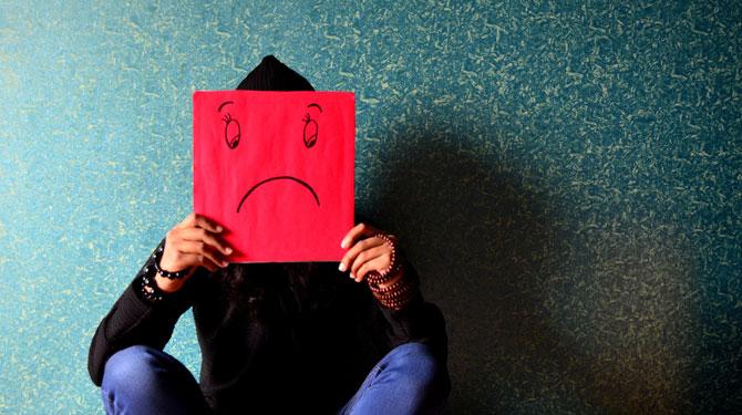Person mit traurigem Smiley vorm Gesicht wegen Hasskommentaren im Netz