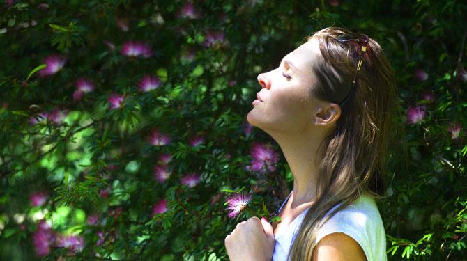 Achtsamkeit und Digital Detox Frau mit geschlossenen Augen im Sonnenlicht
